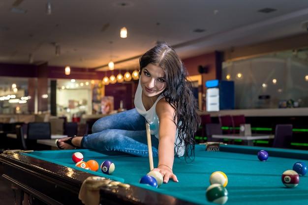 Brunetka siedzi na stole i gra w bilard
