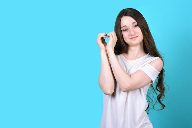 Brunetka składa dłonie w kształcie serca i uśmiecha się.