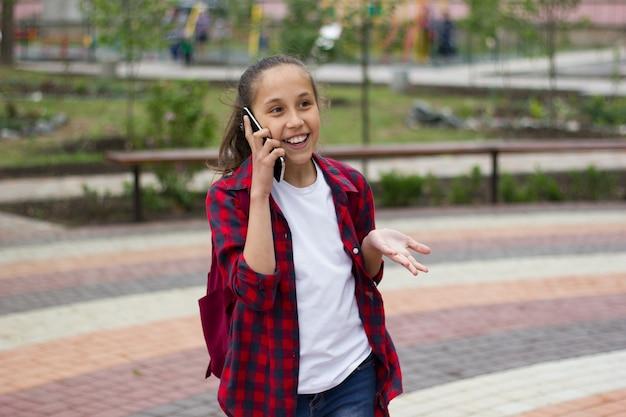 Brunetka śmieje się i rozmawia z entuzjazmem przez telefon