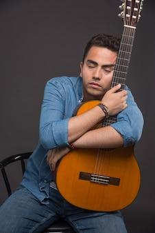 Brunetka śpi mężczyzna ściskając gitarę na ciemnym tle.