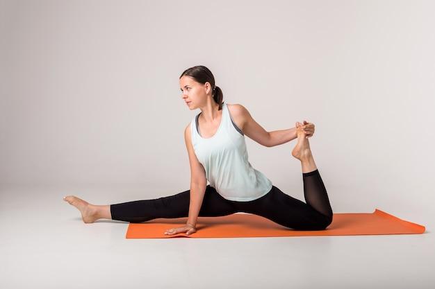 Brunetka sportsmenka siedzi na pomarańczowej macie i wykonuje szpagat z podniesionym kolanem na białym na białym tle