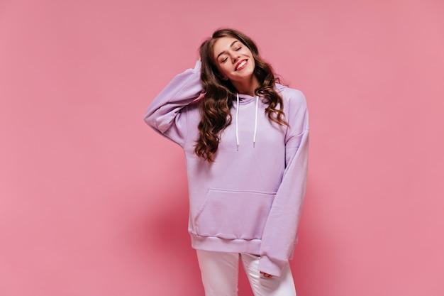 Brunetka szczęśliwa kobieta w fioletowym sportowym garniturze uśmiecha się szczerze