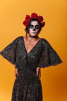 Brunetka szeroko otworzyła oczy ze zdumienia. dziewczyna w sukni z szyfonu i sztuki twarzy na halloween.