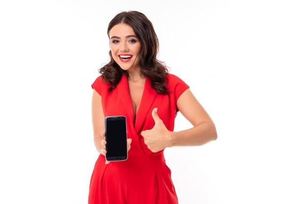 Brunetka trzyma telefon w dłoniach na białym z szerokim uśmiechem pokazuje gest super