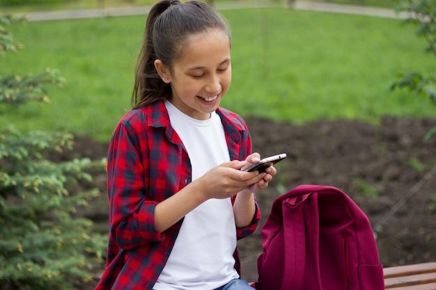 Brunetka uczennica siedzi w parku i komunikuje się w komunikatorze przez telefon komórkowy