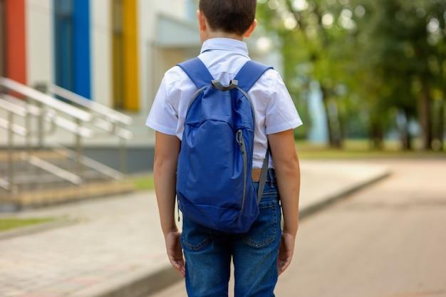 Brunetka uczennica w białej koszuli i niebieskim plecaku idzie do szkoły