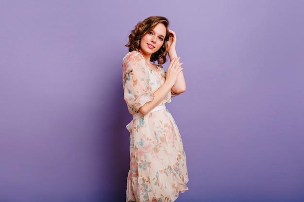 Brunetka ujmująca kobieta w długiej, lekkiej sukience, patrząc z zainteresowaniem do kamery i uśmiechnięty