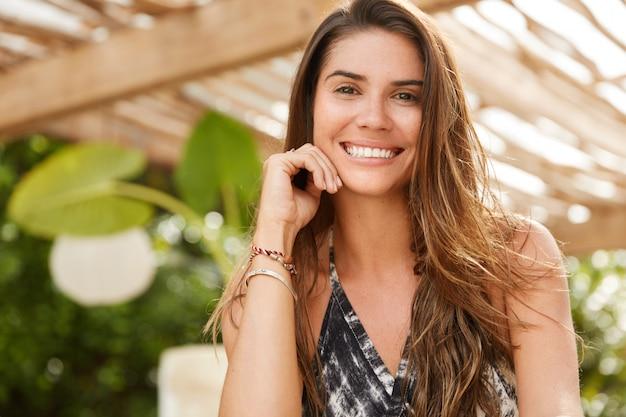 Brunetka uśmiechnięta kobieta siedzi w kawiarni na świeżym powietrzu, ma szeroki uśmiech, dobrze wypoczywa, ma zadowoloną minę, odpoczywa w tropikalnym kurorcie. ładna młoda kobieta odpoczywa w kawiarni na tarasie. pozytywność