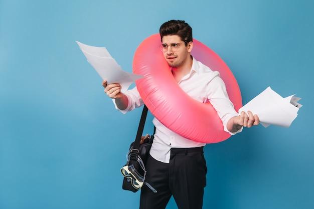 Brunetka w biurze ubrania patrzy na dokumenty z niezadowoleniem. facet wybiera się w podróż i pozuje z różowym nadmuchiwanym kółkiem.