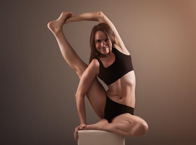 Brunetka w czarnej bieliźnie robi asanę do jogi