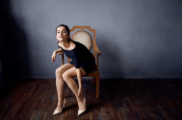 Brunetka w czarnej sukience w pobliżu krzesła luksusowe studio styl życia