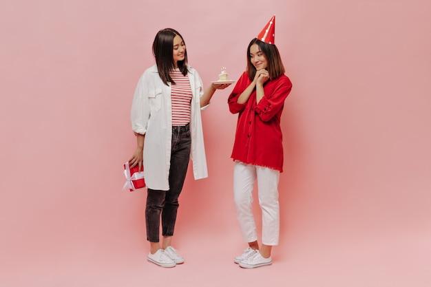 Brunetka w czarnych dżinsach i pasiastym t-shircie prezentuje tort urodzinowy i pudełko upominkowe swojej przyjaciółce