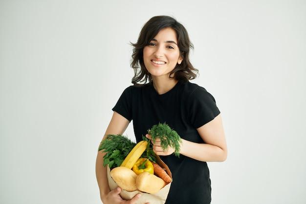 Brunetka w czarnych koszulkach torebkach z warzywami