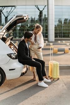 Brunetka w czarnym garniturze i białej koszulce siedzi w bagażniku samochodu