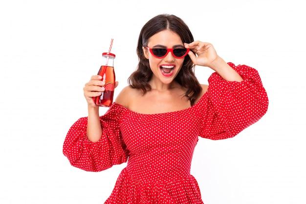 Brunetka w czerwonej sukience z butelką świeżego soku tańczy na białym tle