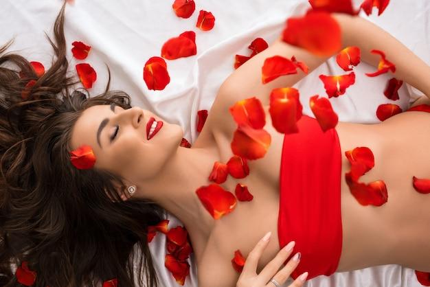 Brunetka w czerwonym topie na łóżku z latającymi płatkami róż