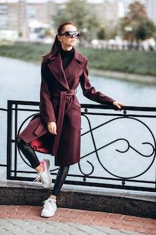 Brunetka w długim bordowym płaszczu spaceruje brzegiem rzeki