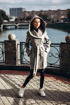 Brunetka w długim szarym płaszczu spaceruje brzegiem rzeki