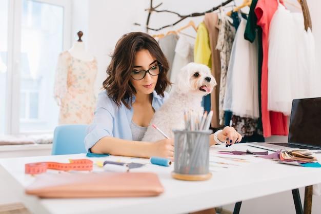 Brunetka w niebieskiej koszuli siedzi przy stole w warsztacie. odczytuje kilka szkiców. pies siedzi na kolanach.