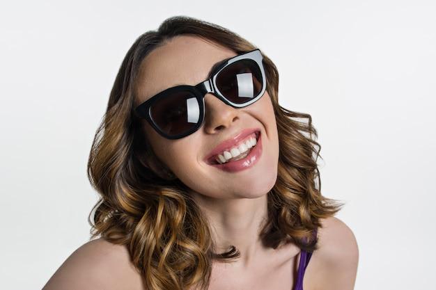 Brunetka w okularach przeciwsłonecznych patrzy na aparat i uśmiecha się