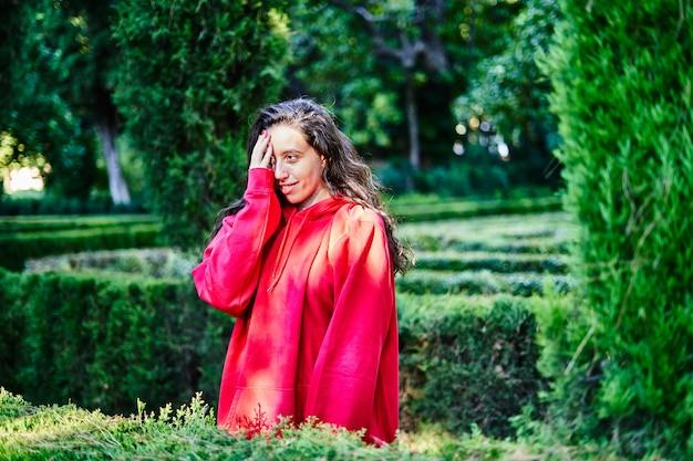 Brunetka w parku zakrywa twarz dłonią