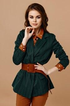 Brunetka w płaszczu trzyma rękę na pasku i beżowej ścianie czerwonych legginsów