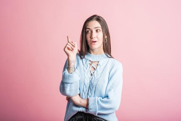 Brunetka w studio na różowym tle wskazuje palcem w górę, pomysł
