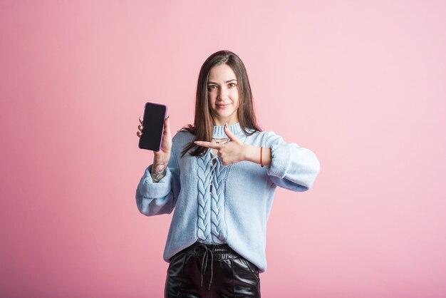 Brunetka wskazuje palcem na smartfona w studio na różowym tle