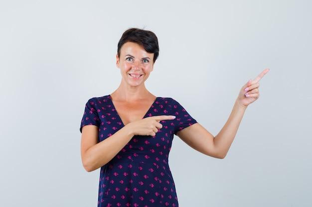 Brunetka wskazuje prawy górny róg palcami wskazującymi w fioletowo-czerwonej wzorzystej sukience i wygląda optymistycznie z przodu.