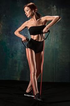 Brunetka wysportowana kobieta ćwiczenia z gumową taśmą