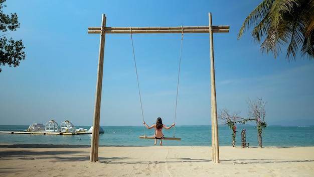 Brunetka z długimi włosami huśta się na piaszczystej plaży i cieszy się krajobrazem pod zielonymi palmami na tle błękitnego nieba