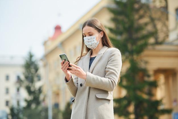Brunetka z długimi włosami w medycznej masce na twarz, aby uniknąć rozprzestrzeniania się koronawirusa, czyta wiadomości na smartfonie na starej ulicy. kobieta w masce przeciw covid-19 utrzymuje dystans społeczny.