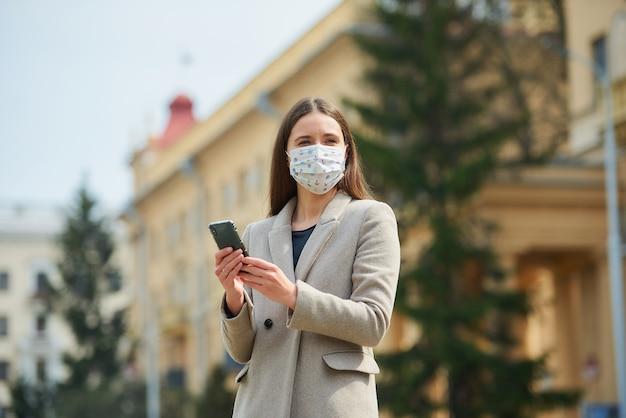Brunetka z długimi włosami w medycznej masce na twarz, aby uniknąć rozprzestrzeniania się koronawirusa, przeszukuje wiadomości na smartfonie na starej ulicy. kobieta w masce przeciw covid-19 utrzymuje dystans społeczny.