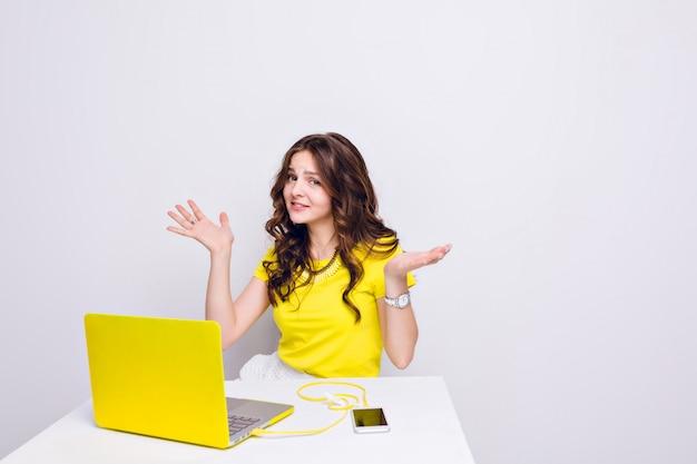 Brunetka z kręconymi włosami wygląda na zdezorientowaną siedząc przed laptopem w żółtej obudowie.