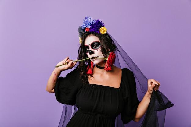 Brunetka z kwiatami we włosach wygląda przebiegle, pozując z czerwoną różą. portret kobiety w masce czaszki i czarną zasłonę.