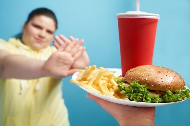 Brunetka z nadwagą i zamkniętymi oczami zbudowała ramiona jak krzyż, aby pokazać, że nie chce jeść fast foodów na białym talerzu. młoda ładna dama dokonuje właściwego wyboru dla swojego zdrowego stylu życia