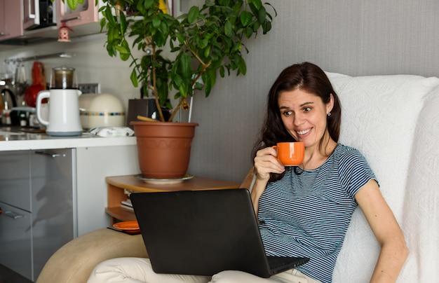 Brunetka z pomarańczową filiżanką jest zaskoczona i patrząc na swojego laptopa podczas rozmowy wideo w swoim mieszkaniu. zabawne powitanie online. używać komputera. edukacja i praca online na odległość