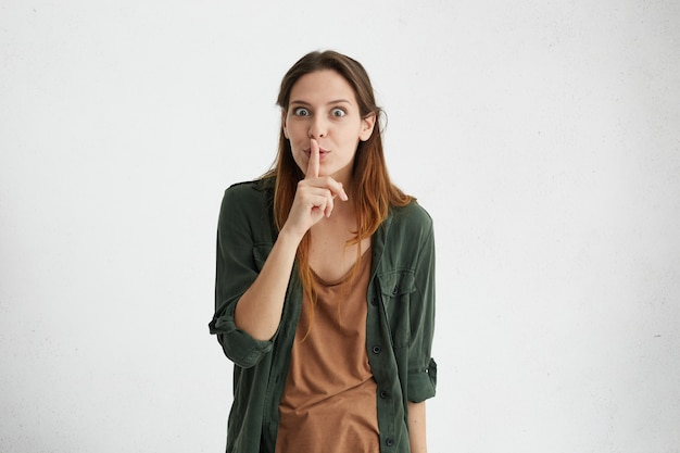 Brunetka z prostymi włosami na sobie zieloną kurtkę, trzymając palec wskazujący na ustach, robiąc znak ciszy, prosząc, aby nie być hałaśliwym.