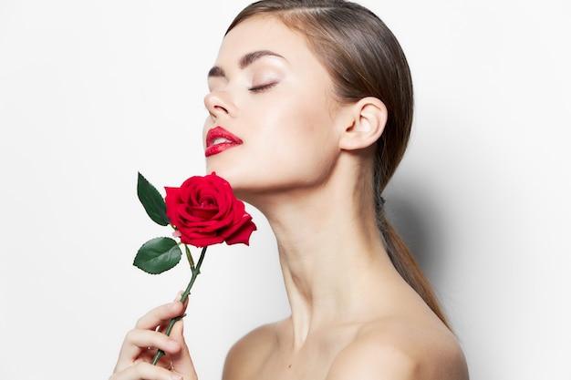 Brunetka z różą oczy zamknięte nagimi ramionami modelują czerwone usta