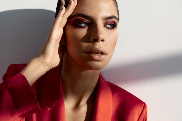 Brunetka z wieczorowym makijażem i w czerwonej kurtce trzyma rękę w pobliżu głowy przycięty widok