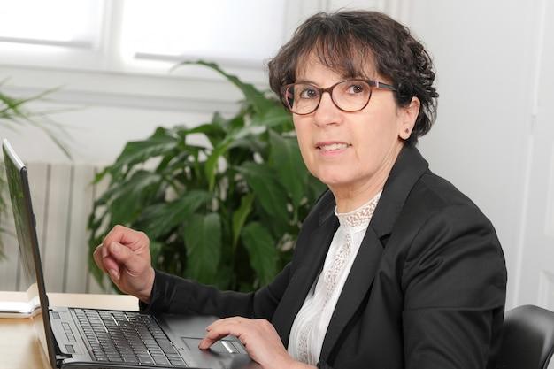 Brunetki dojrzała kobieta używa laptop