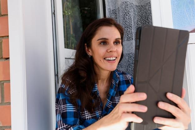 Brunetki dziewczyna ono uśmiecha się patrzejący jej pastylkę robi selfie lub wideo rozmowie w balkonie. zabawne powitanie online