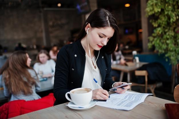 Brunetki dziewczyna siedzi w kawiarni z filiżanką cappuccino, słucha muzyki na słuchawkach i pisze niektóre dokumenty.