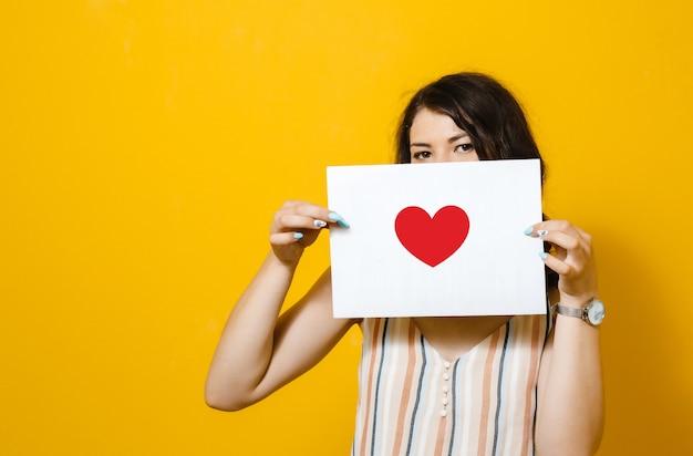 Brunetki dziewczyna trzyma biały puste miejsce z sercem na żółtej ścianie