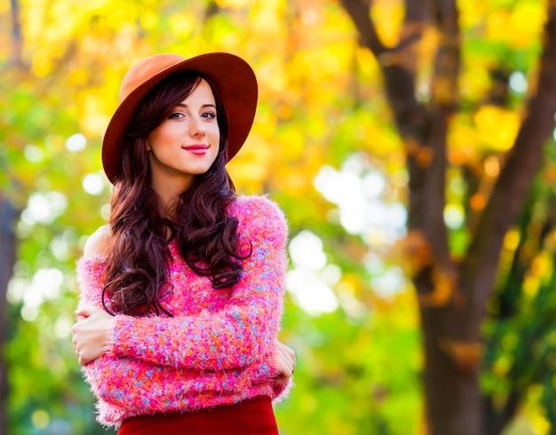Brunetki dziewczyna w różowym pulowerze w jesień parku.
