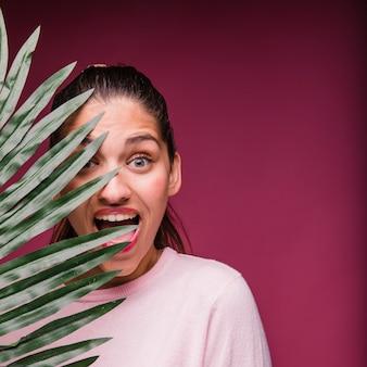 Brunetki dziewczyna z tropikalnym liściem