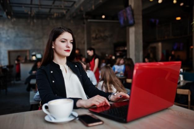 Brunetki dziewczyny obsiadanie w kawiarni z filiżanką cappuccino, pracuje z czerwonym laptopem.