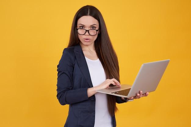 Brunetki gira w kostiumu pozuje z laptopem odizolowywającym.