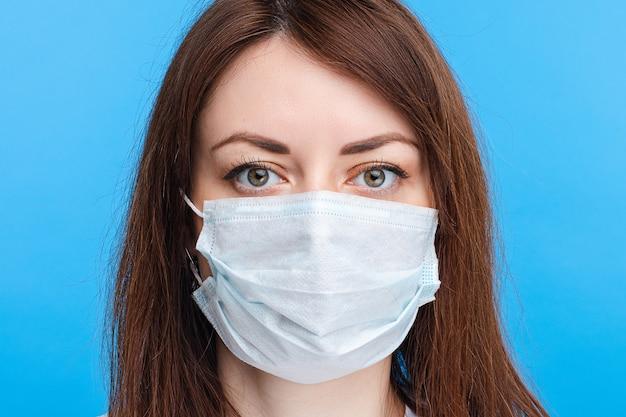 Brunetki kobieta jest ubranym aseptyczną maskę