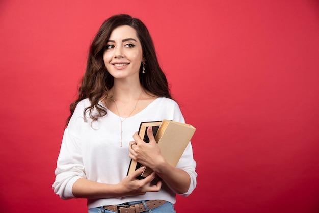 Brunetki kobieta stoi na czerwonym tle z książkami. zdjęcie wysokiej jakości